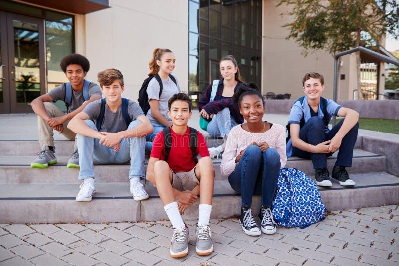 Πορτρέτο της συνεδρίασης ομάδας σπουδαστών γυμνασίου έξω από τα κτήρια κολλεγίου στοκ εικόνα