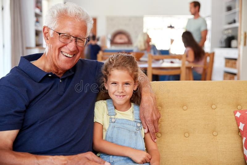 Πορτρέτο της συνεδρίασης παππούδων με την εγγονή στον καναπέ στο σπίτι στοκ εικόνες
