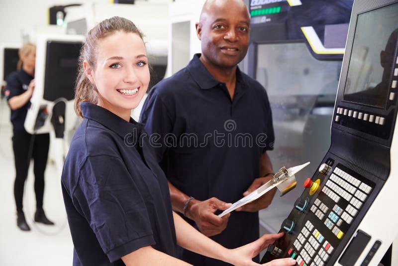 Πορτρέτο της συνεργασίας μαθητευόμενων με το μηχανικό CNC στη μηχανή στοκ φωτογραφία με δικαίωμα ελεύθερης χρήσης