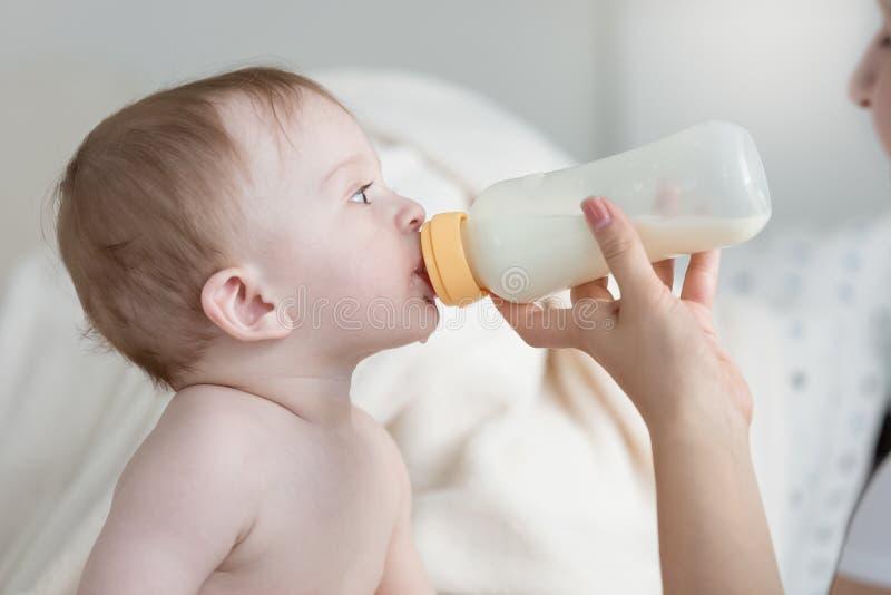 Πορτρέτο της συνεδρίασης αγοράκι στο κρεβάτι και της κατανάλωσης του γάλακτος από το μπουκάλι στοκ εικόνες