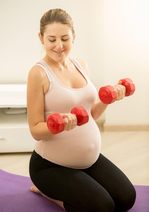 Πορτρέτο της συνεδρίασης εγκύων γυναικών στους αλτήρες χαλιών και εκμετάλλευσης στοκ εικόνες με δικαίωμα ελεύθερης χρήσης