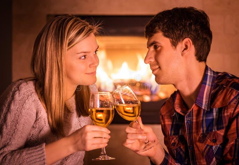 Πορτρέτο της συνεδρίασης ζευγών κοντά στην εστία και το κρασί κατανάλωσης στοκ φωτογραφίες με δικαίωμα ελεύθερης χρήσης