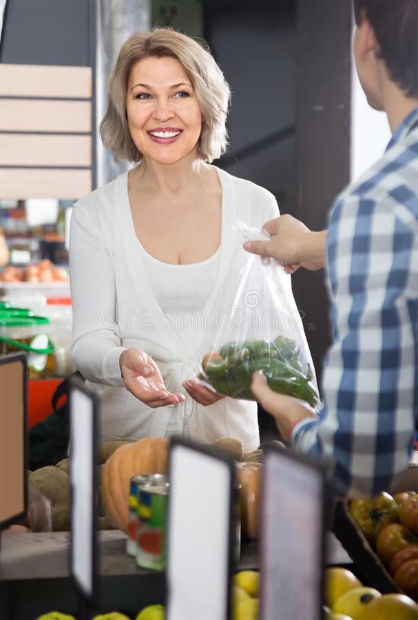 Πορτρέτο της συνηθισμένης ώριμης γυναίκας που αγοράζει το πράσινο πιπέρι στο παντοπωλείο στοκ φωτογραφίες