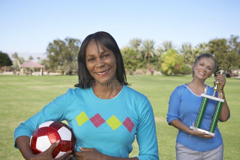 Πορτρέτο της σφαίρας και του τροπαίου ποδοσφαίρου εκμετάλλευσης γυναικών στο πάρκο στοκ φωτογραφίες