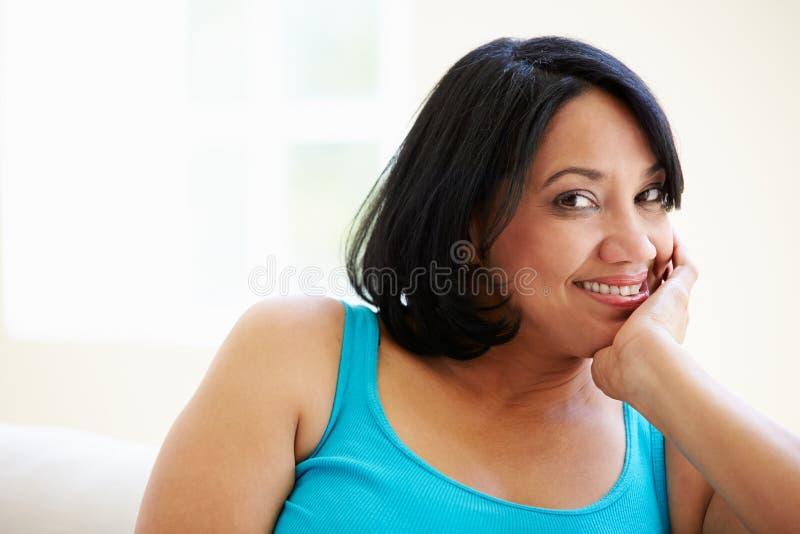 Πορτρέτο της υπέρβαρης συνεδρίασης γυναικών στον καναπέ στοκ εικόνα