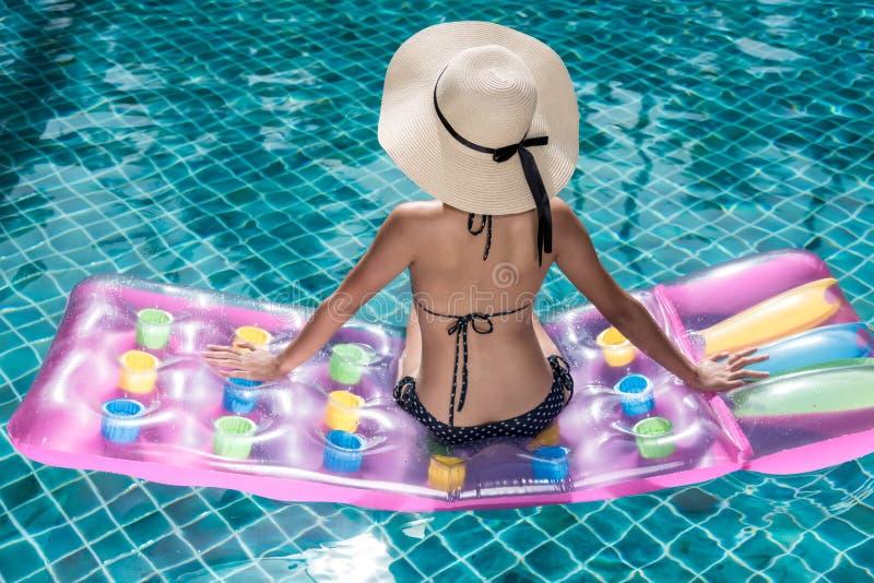 Πορτρέτο της χαλάρωσης γυναικών beautifu στο μπικίνι και το μεγάλο καπέλο στο swi στοκ φωτογραφίες