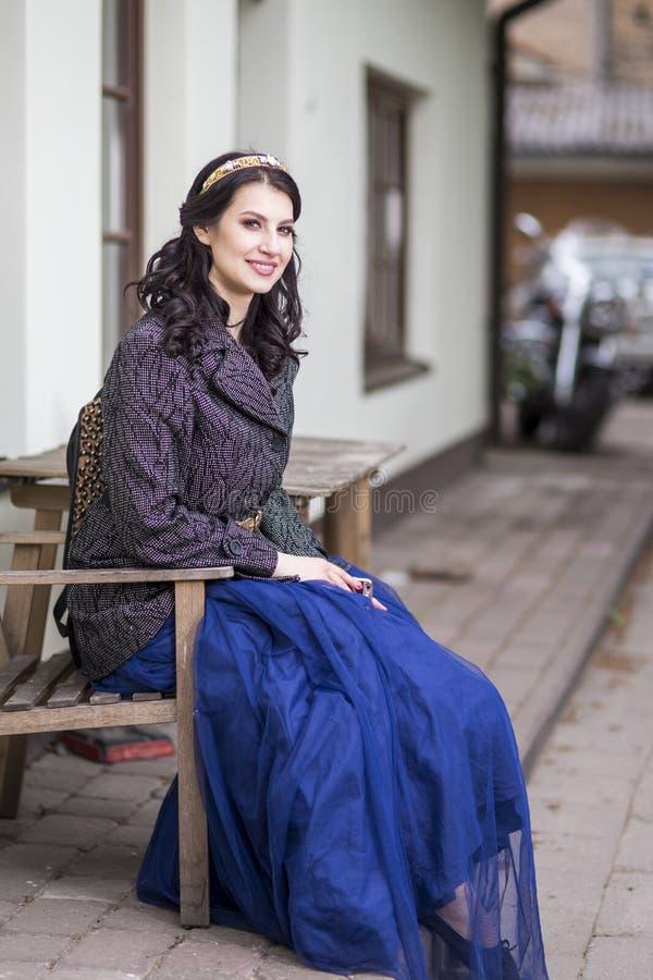 Πορτρέτο της χαμογελαστής ευτυχισμένης κοπέλας του Καυκάσου με τον Diadem να ποζάρει σε εξωτερικό χώρο στοκ εικόνα