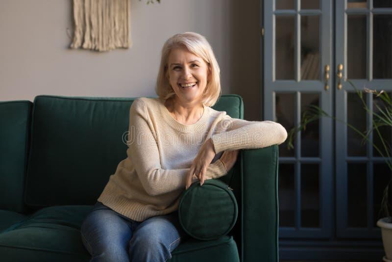 Πορτρέτο της χαμογελώντας γκρίζας μαλλιαρής ώριμης γυναίκας που εξετάζει τη κάμερα στοκ εικόνες με δικαίωμα ελεύθερης χρήσης