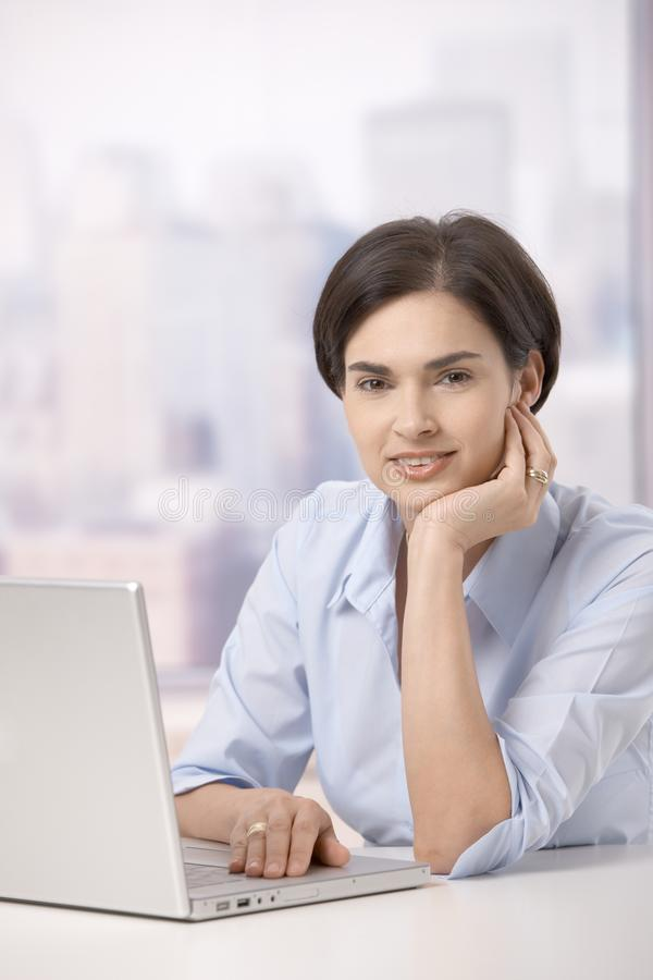 Πορτρέτο της χαμογελώντας γυναίκας με τον υπολογιστή στοκ εικόνες