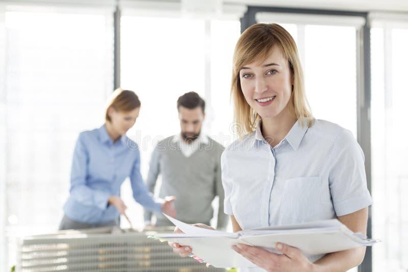 Πορτρέτο της χαμογελώντας επιχειρηματία με το αρχείο που στέκεται ενάντια στους συναδέλφους και το πρόγραμμα στοκ εικόνες