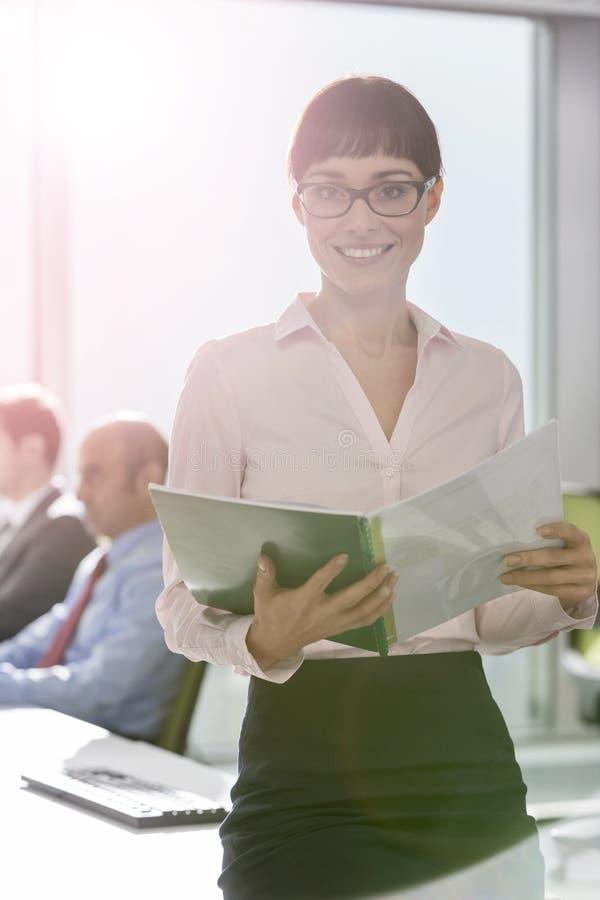 Πορτρέτο της χαμογελώντας επιχειρηματία που στέκεται με το έγγραφο στο σύγχρονο γραφείο στοκ φωτογραφίες με δικαίωμα ελεύθερης χρήσης
