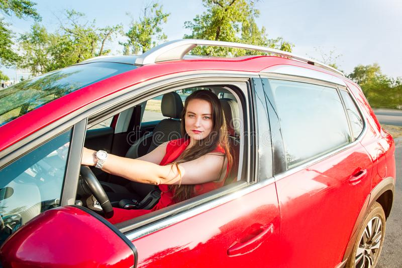 Πορτρέτο της χαμογελώντας επιχειρησιακής κυρίας, καυκάσιος νέος οδηγός γυναικών στα κόκκινα ενδύματα που εξετάζουν τη κάμερα και  στοκ φωτογραφία