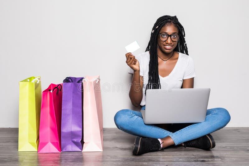 Πορτρέτο της χαμογελώντας νέας αμερικανικής γυναίκας afro που χρησιμοποιεί το lap-top καθμένος σε ένα πάτωμα με τις τσάντες πλησί στοκ εικόνα με δικαίωμα ελεύθερης χρήσης