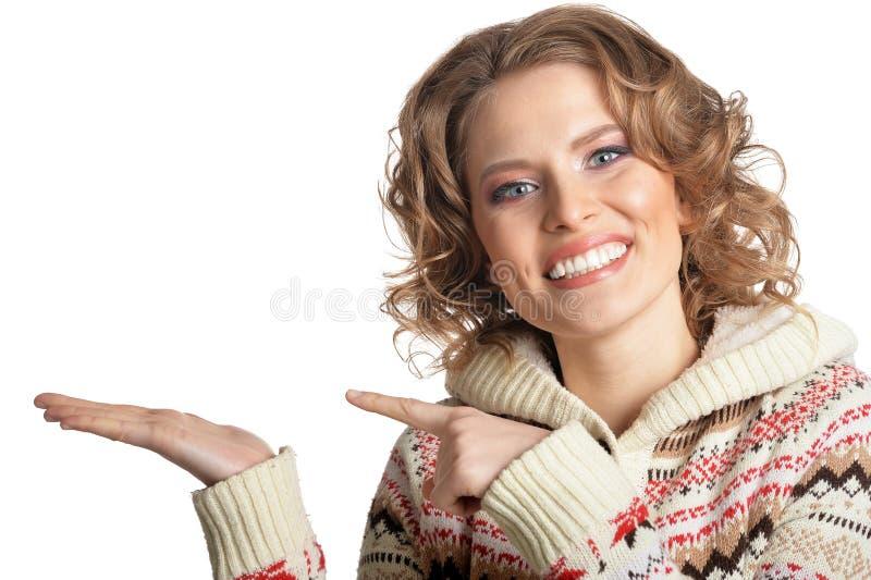 Πορτρέτο της χαμογελώντας νέας γυναίκας που δείχνει το αριστερό στο άσπρο υπόβαθρο στοκ εικόνα με δικαίωμα ελεύθερης χρήσης