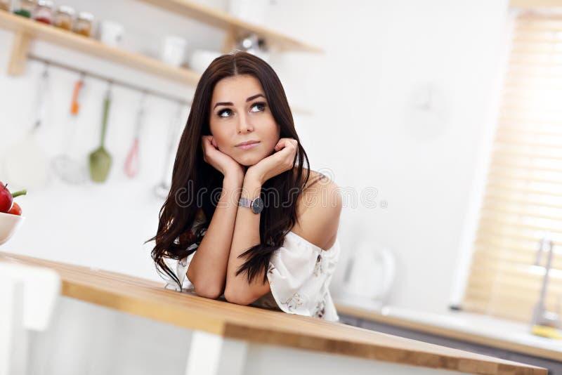 Πορτρέτο της χαμογελώντας νέας νοικοκυράς στη σύγχρονη κουζίνα στοκ φωτογραφίες