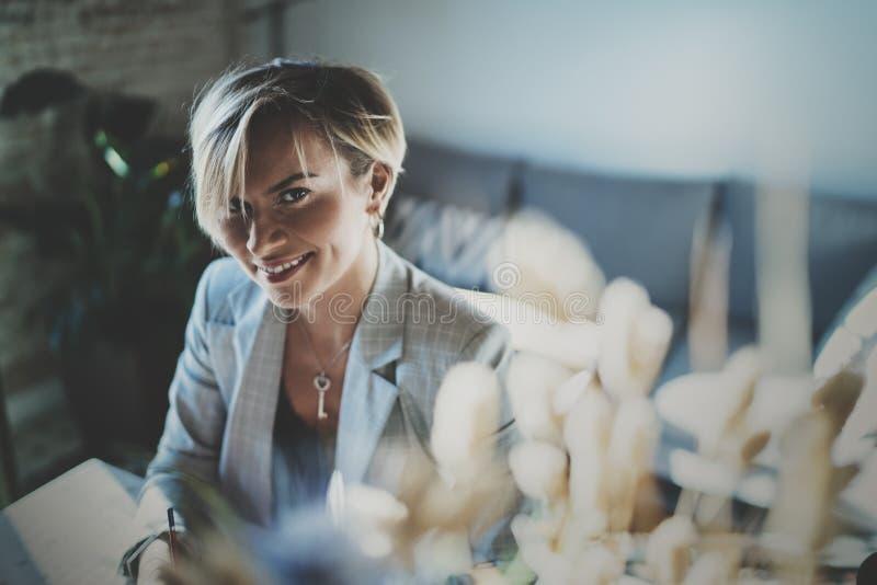 Πορτρέτο της χαμογελώντας νέας όμορφης γυναίκας στο καθιστικό όμορφο χαμόγελο κοριτσιών εξετάζοντας τη κάμερα θαμπάδων στοκ εικόνες