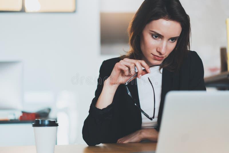 Πορτρέτο της χαμογελώντας όμορφης επιχειρηματία που χρησιμοποιεί το φορητό προσωπικό υπολογιστή στο σύγχρονο γραφείο ανασκόπηση π στοκ φωτογραφία