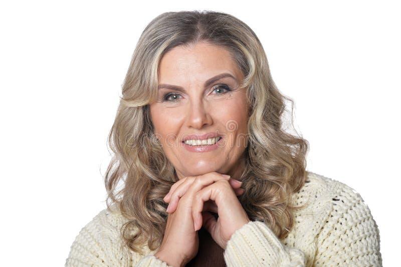 Πορτρέτο της χαμογελώντας ώριμης γυναίκας που εξετάζει τη κάμερα απομονωμένης στοκ φωτογραφία