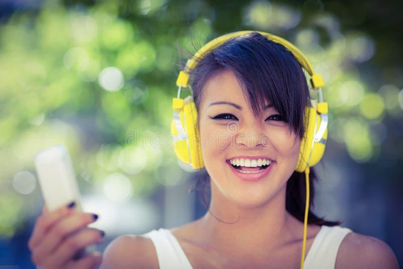 Πορτρέτο της χαμογελώντας αθλητικής γυναίκας που φορά τα κίτρινα ακουστικά και που κρατά το smartphone στοκ εικόνες