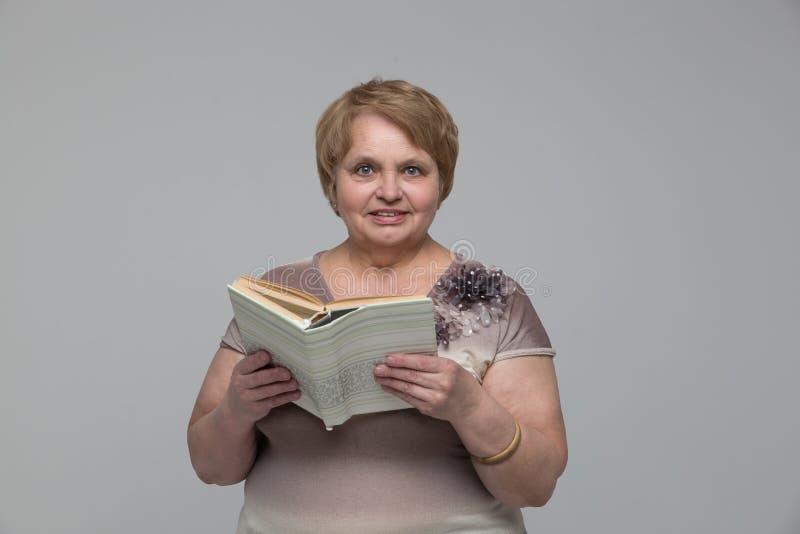 Πορτρέτο της χαμογελώντας ανώτερης γυναίκας με ένα βιβλίο στοκ εικόνα με δικαίωμα ελεύθερης χρήσης
