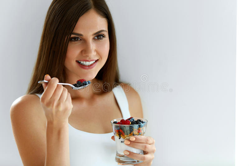 Πορτρέτο της χαμογελώντας γυναίκας που τρώει το γιαούρτι με τις βρώμες και τα μούρα στοκ εικόνες