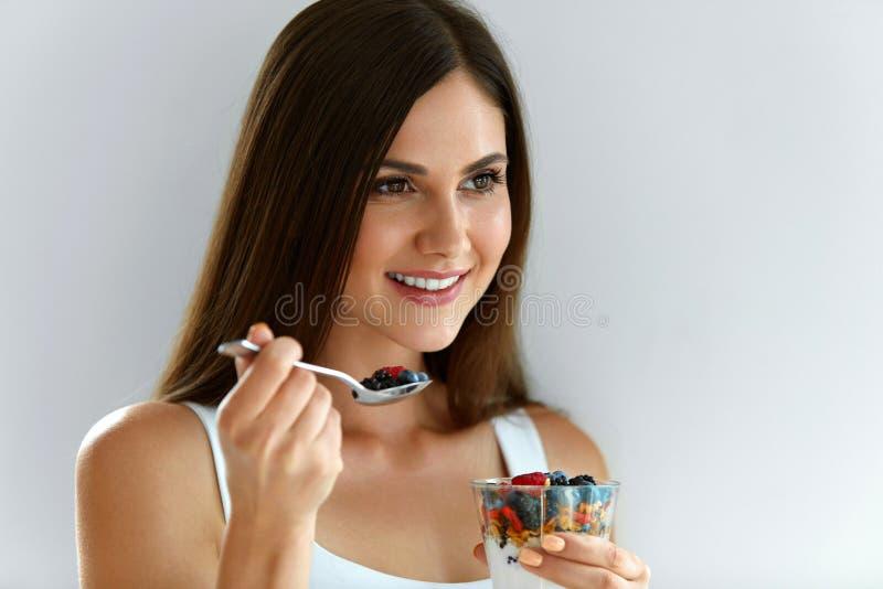 Πορτρέτο της χαμογελώντας γυναίκας που τρώει το γιαούρτι με τις βρώμες και τα μούρα στοκ φωτογραφίες