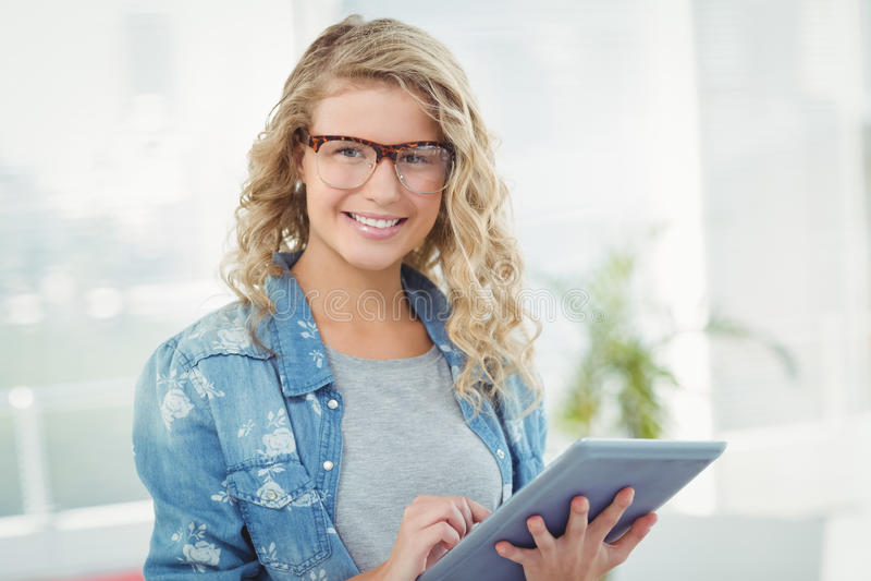 Πορτρέτο της χαμογελώντας γυναίκας που φορά eyeglasses χρησιμοποιώντας την ψηφιακή ταμπλέτα στοκ εικόνα