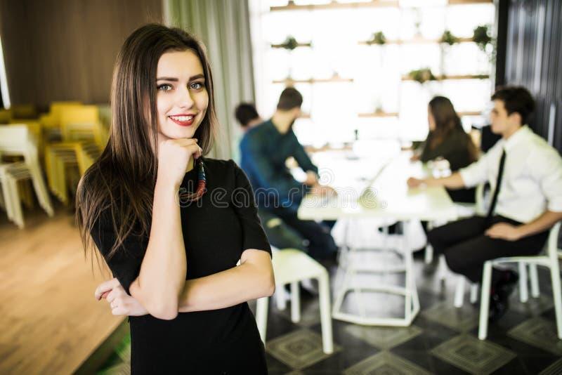 Πορτρέτο της χαμογελώντας επιχειρηματία μπροστά από τη διαφορετική επιχειρησιακή ομάδα στοκ φωτογραφία