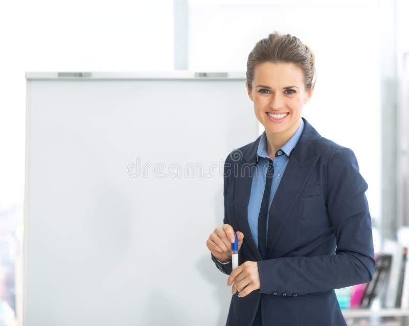Πορτρέτο της χαμογελώντας επιχειρησιακής γυναίκας flipchart πλησίον στοκ φωτογραφία με δικαίωμα ελεύθερης χρήσης