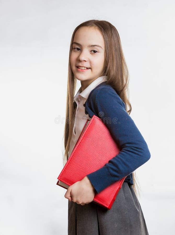 Πορτρέτο της χαμογελώντας μαθήτριας brunette που κρατά το μεγάλο βιβλίο στοκ φωτογραφία με δικαίωμα ελεύθερης χρήσης