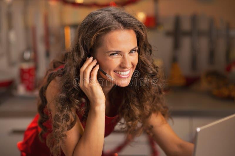 Πορτρέτο της χαμογελώντας νέας γυναίκας που έχει την τηλεοπτική συνομιλία στο lap-top στοκ φωτογραφία