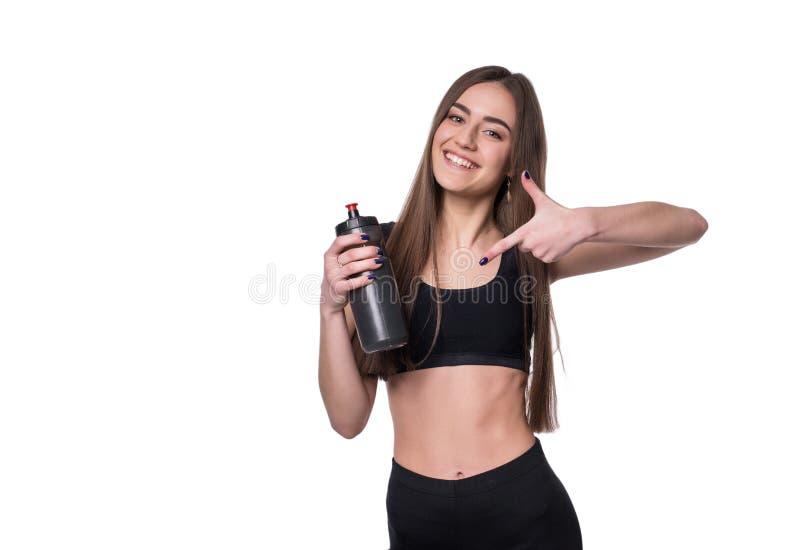 Πορτρέτο της χαμογελώντας νέας φίλαθλης γυναίκας με μια τοποθέτηση μπουκαλιών νερό στο στούντιο που απομονώνεται στο άσπρο υπόβαθ στοκ εικόνες με δικαίωμα ελεύθερης χρήσης
