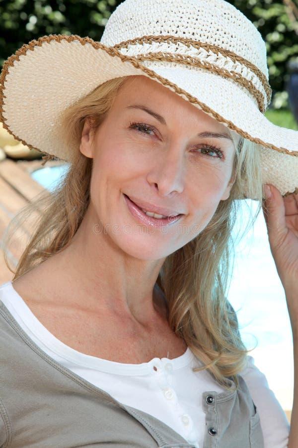 Πορτρέτο της χαμογελώντας ξανθής ώριμης γυναίκας που φορά το καπέλο στοκ εικόνα