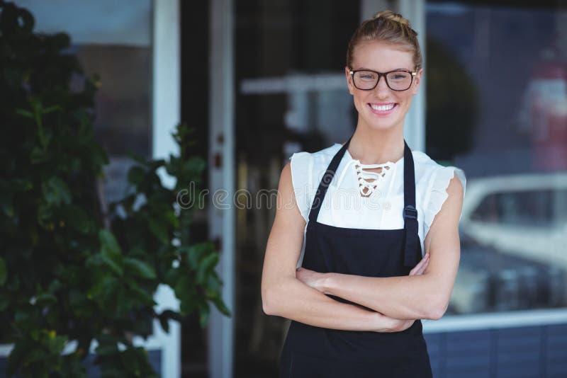 Πορτρέτο της χαμογελώντας σερβιτόρας που στέκεται με τα όπλα που διασχίζονται στοκ φωτογραφίες με δικαίωμα ελεύθερης χρήσης