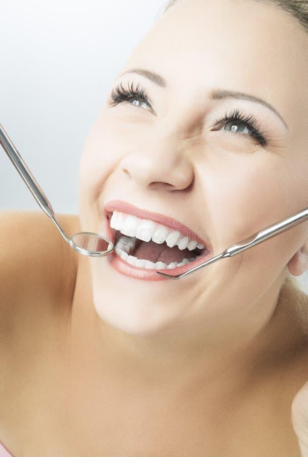 Πορτρέτο της χαμογελώντας υγιούς γυναίκας με τον καθρέφτη και Spatul οδοντιάτρων στοκ εικόνα