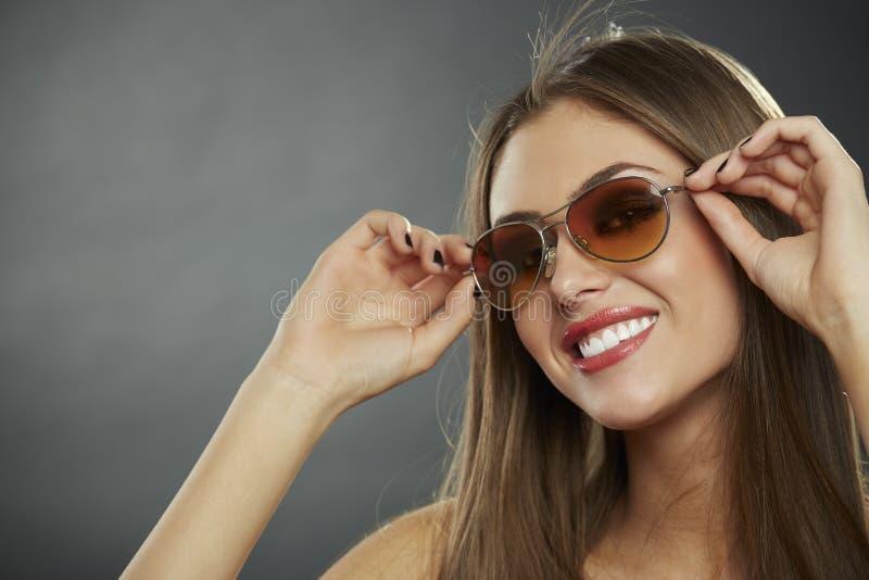 Γυναίκα που φορά τα γυαλιά ηλίου και το χαμόγελο στοκ εικόνες