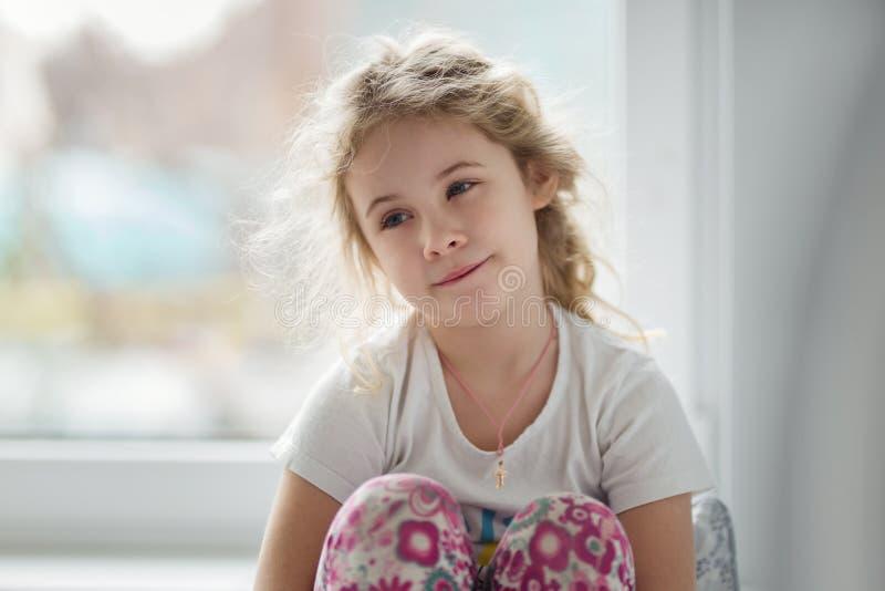 Πορτρέτο της χαριτωμένης ξανθής συνεδρίασης κοριτσιών παιδιών κοντά στο παράθυρο στοκ εικόνα με δικαίωμα ελεύθερης χρήσης