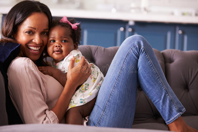 Πορτρέτο της χαλάρωσης γυναικών στο σπίτι με την κόρη μικρών παιδιών της στοκ εικόνα