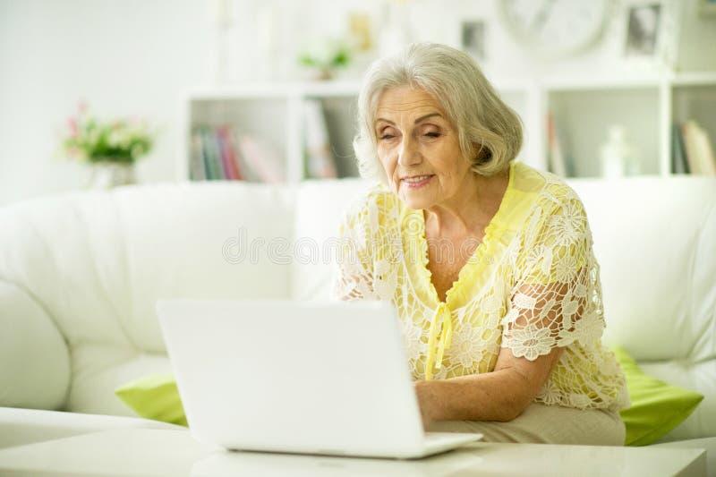 Πορτρέτο της όμορφης ανώτερης συνεδρίασης γυναικών στον πίνακα με το lap-top στοκ εικόνες με δικαίωμα ελεύθερης χρήσης