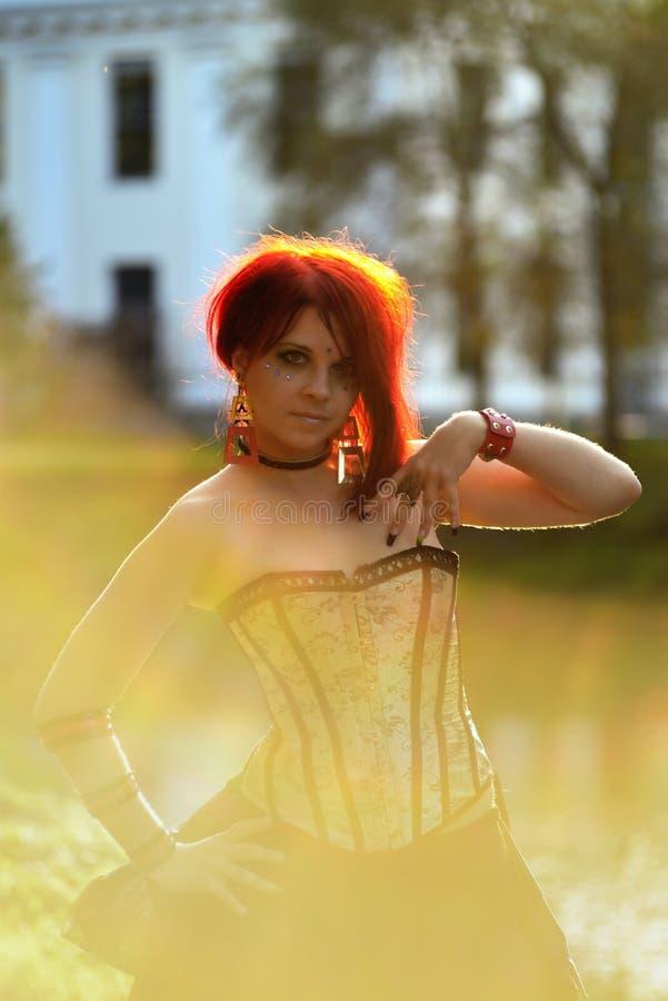 Πορτρέτο της όμορφης γυναίκας κόκκινος-τρίχας στο φυσικό υπόβαθρο στο βικτοριανό κοστούμι στοκ εικόνες