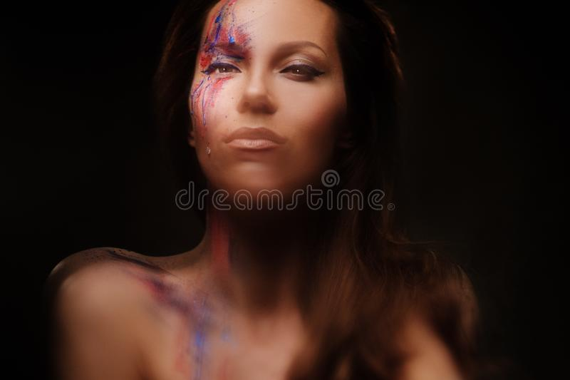 Πορτρέτο της όμορφης γυναίκας με δημιουργικό που χρωματίζεται makeup σε ένα σκοτεινό υπόβαθρο στοκ εικόνα