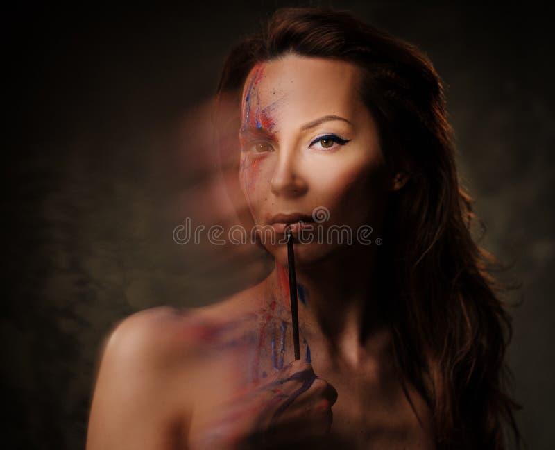 Πορτρέτο της όμορφης γυναίκας με δημιουργικό που χρωματίζεται makeup σε ένα σκοτεινό υπόβαθρο στοκ φωτογραφίες