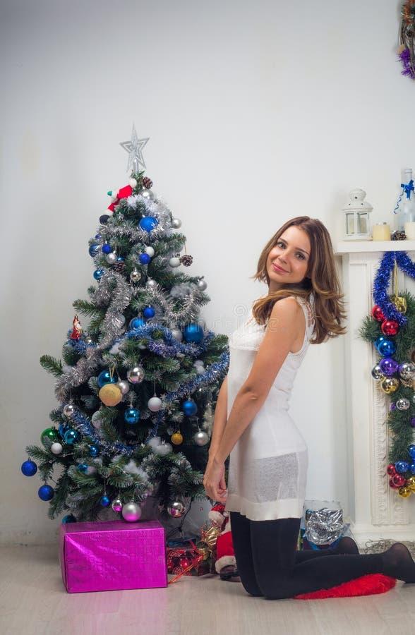 Πορτρέτο της όμορφης γυναίκας με τα χριστουγεννιάτικα δώρα κοντά στο χριστουγεννιάτικο δέντρο στοκ φωτογραφία με δικαίωμα ελεύθερης χρήσης
