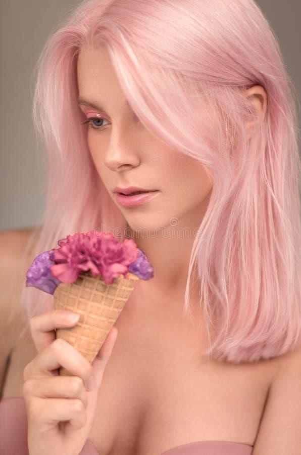 Πορτρέτο της όμορφης γυναίκας με τη ρόδινα τρίχα και το παγωτό στοκ εικόνες