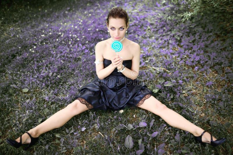 Πορτρέτο της όμορφης γυναίκας με τη συνεδρίαση καραμελών lollipop στο λιβάδι στοκ φωτογραφίες