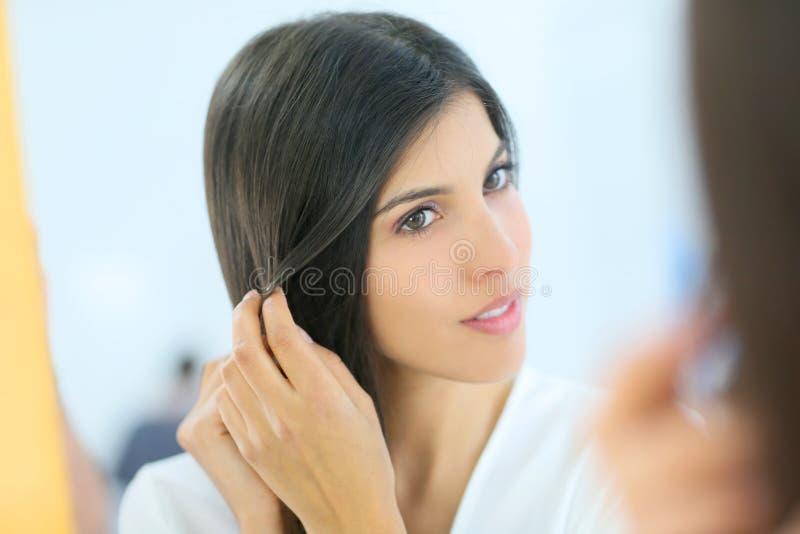 Πορτρέτο της όμορφης γυναίκας που εξετάζει το miror στοκ εικόνες
