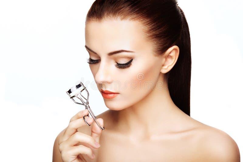 Πορτρέτο της όμορφης γυναίκας που κάνει την μπούκλα eyelashes στοκ εικόνες