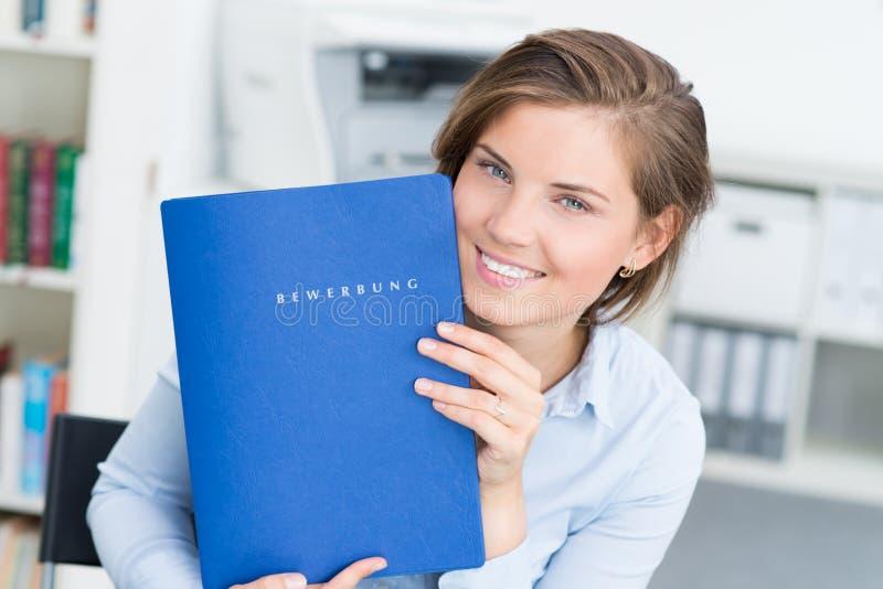 πορτρέτο της όμορφης γυναίκας που παρουσιάζει χαρτοφυλάκιό της στοκ εικόνες