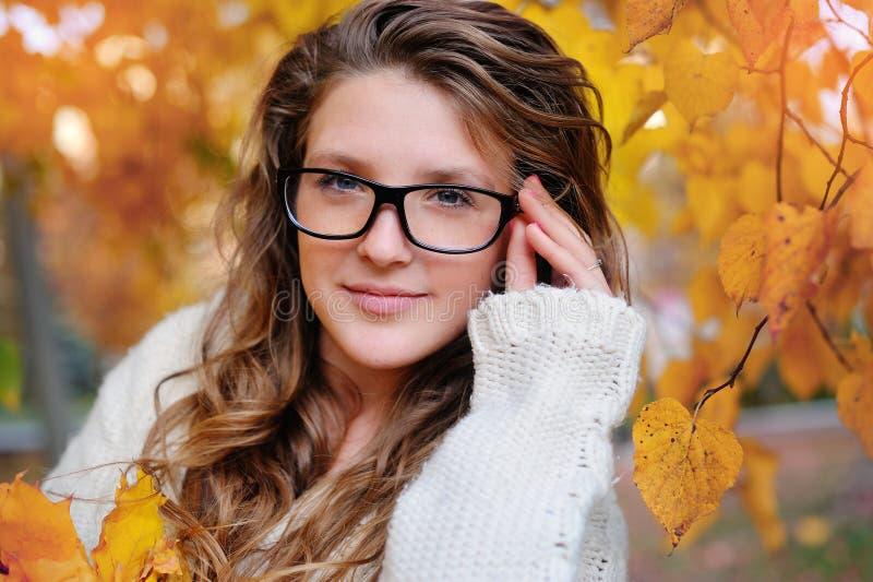 Πορτρέτο της όμορφης γυναίκας που φορά τα γυαλιά μόδας κατά τη διάρκεια του φθινοπώρου στοκ εικόνα