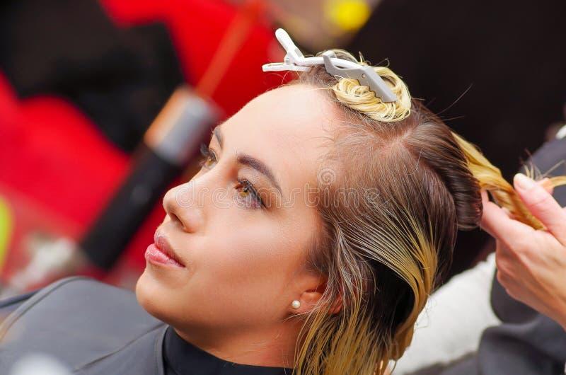 Πορτρέτο της όμορφης γυναίκας σε ένα κομμωτήριο με μια τέμνουσα τρίχα πελατών ` s κομμωτών σε ένα θολωμένο υπόβαθρο στοκ εικόνα